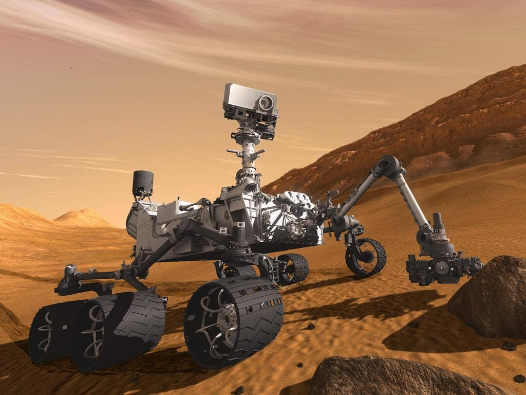 An artist's impression of the Mars Science Laboratory's robot, Curiosity, at work on the surface of Mars
