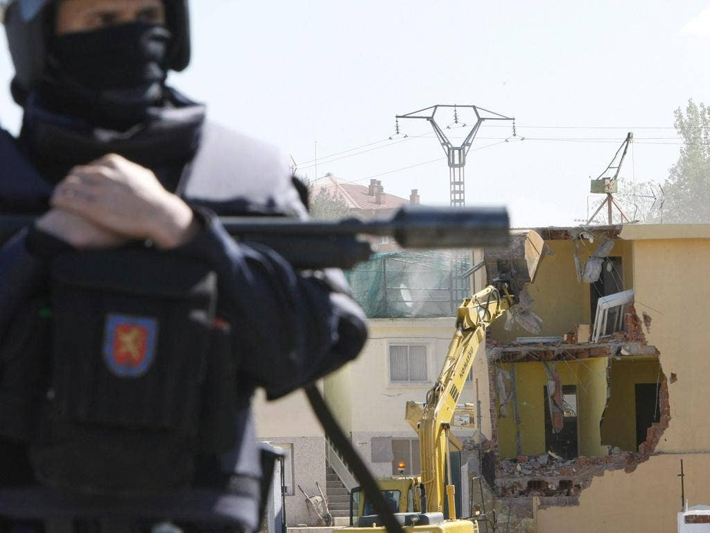 One of the over 400 police officers who kept watch over the pulling down of two evicted buildings in Canada Real Galiana near Madrid in 2008