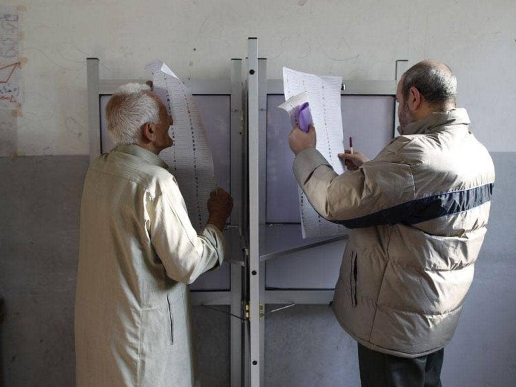 Egyptians read their ballots at a booth before casting their votes at a polling station