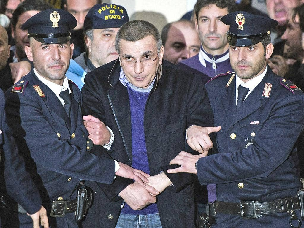 Policemen lead Michele Zagaria away after he was dug out of a bunker built under his home near Naples