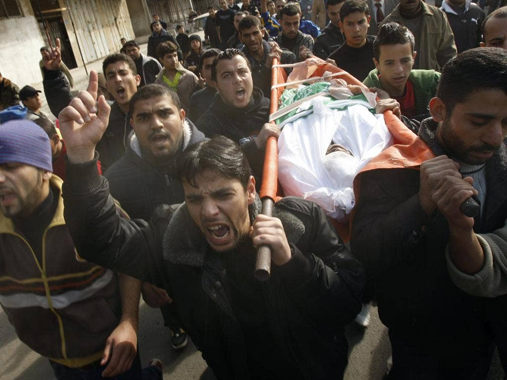 The body of a Palestinian killed in his home by an Israeli air strike is carried through Gaza City