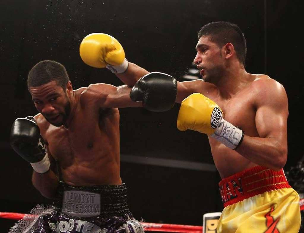Amir Khan and Lamont Peterson exchange punches during their WBA Super Lightweight and IBF Junior Welterweight title fight in Washington
