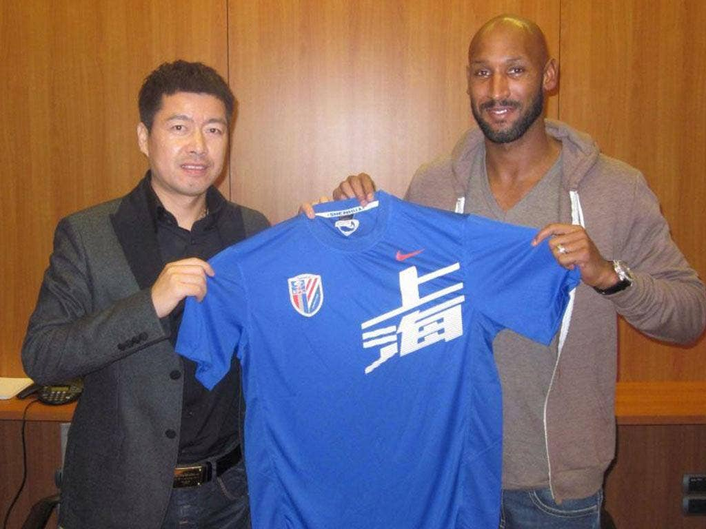 Nicolas Anelka (right) poses with his new shirt and Shanghai Shenhua club investor Zhu Jun after signing a two-year deal
