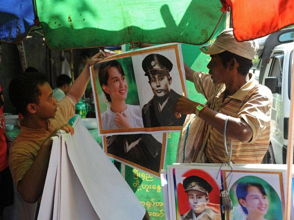 A vendor (R) sells posters of Myanmar's independence hero General Aung San and his daughter democracy icon Aung San Suu Kyi