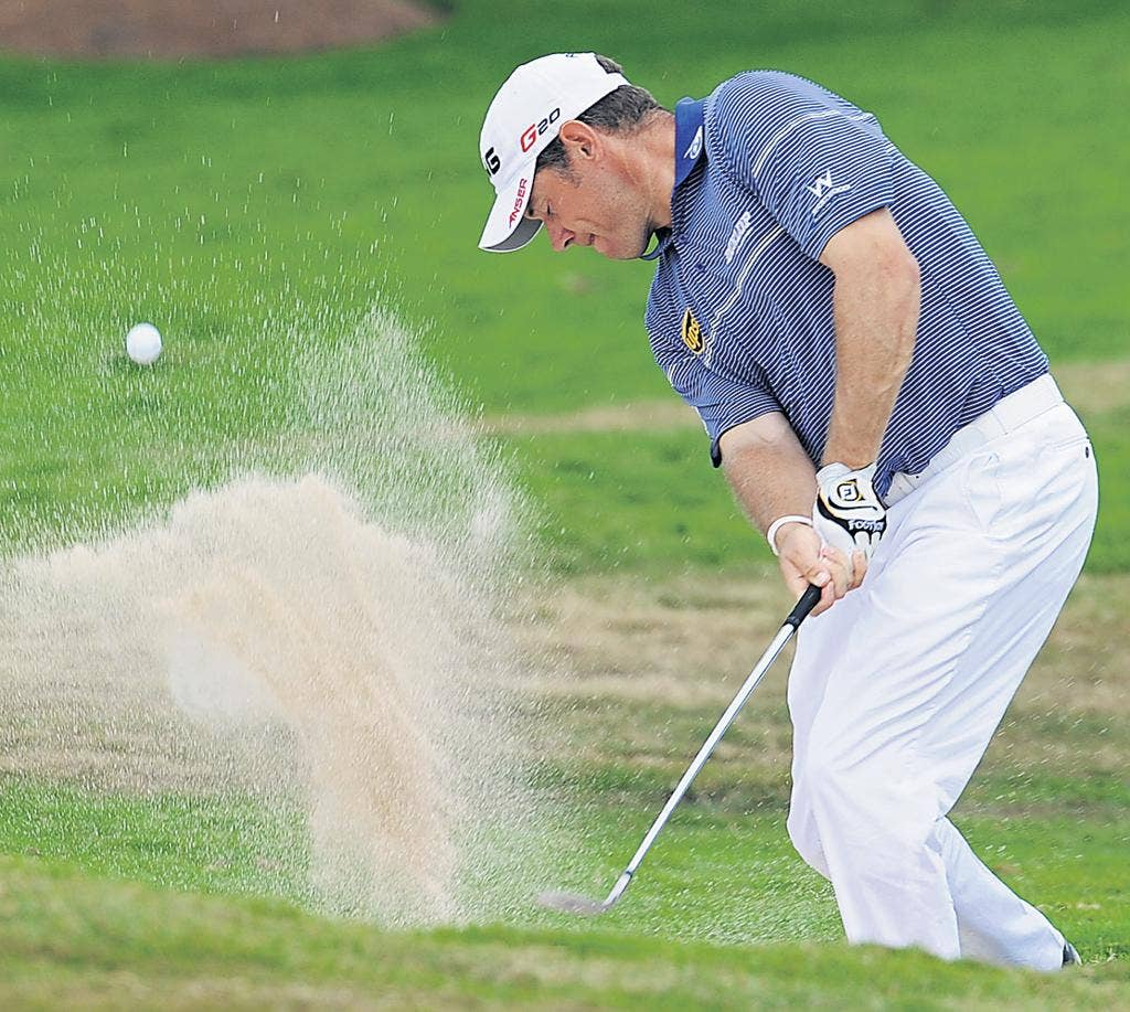 Trap negotiated: Lee Westwood splashes out of a bunker during his third-round 73 in Bangkok yesterday