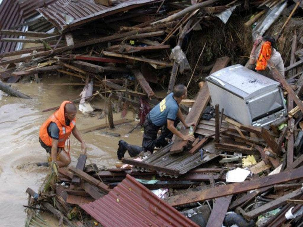 Police approach a distraught resident following a flash flood that inundated Cagayan de Oro city, Philippines