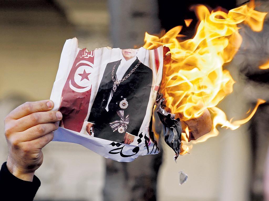 A Tunisian burns an image of his country's former ruler, Zine al-Abidine Ben Ali