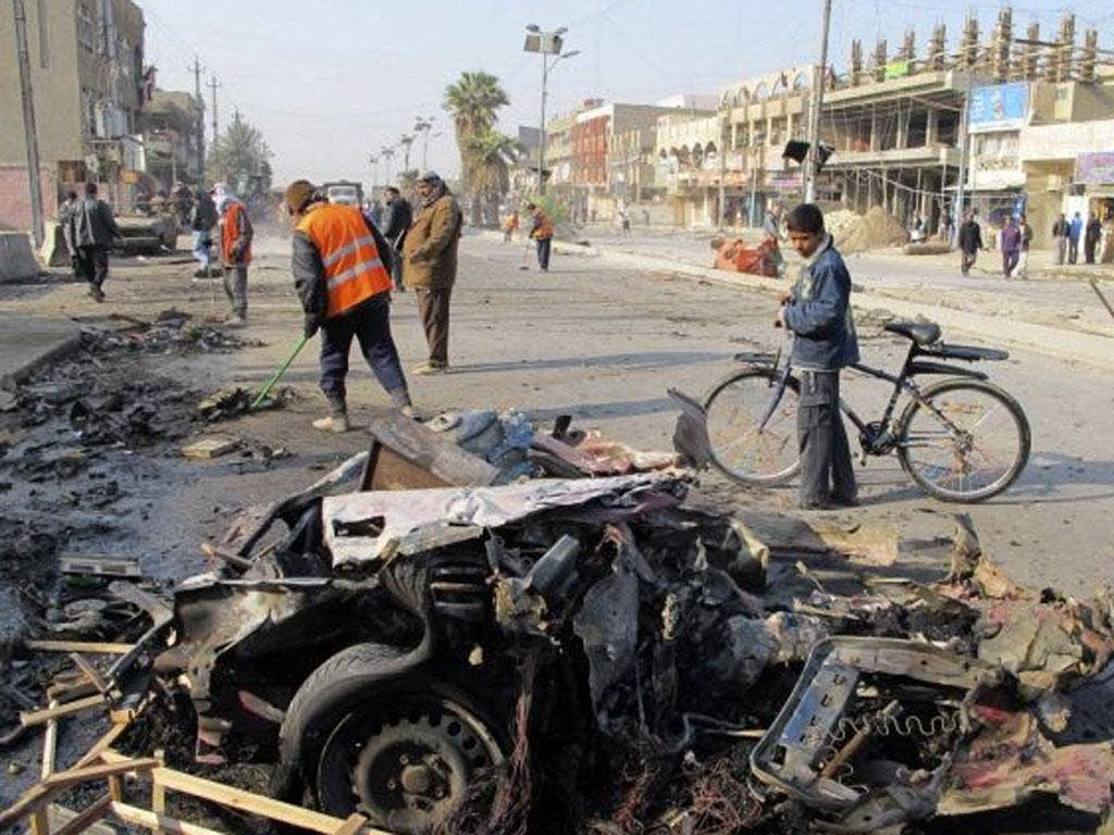 A boy stands near the site of a car bomb attack in Baghdad's Shaab District