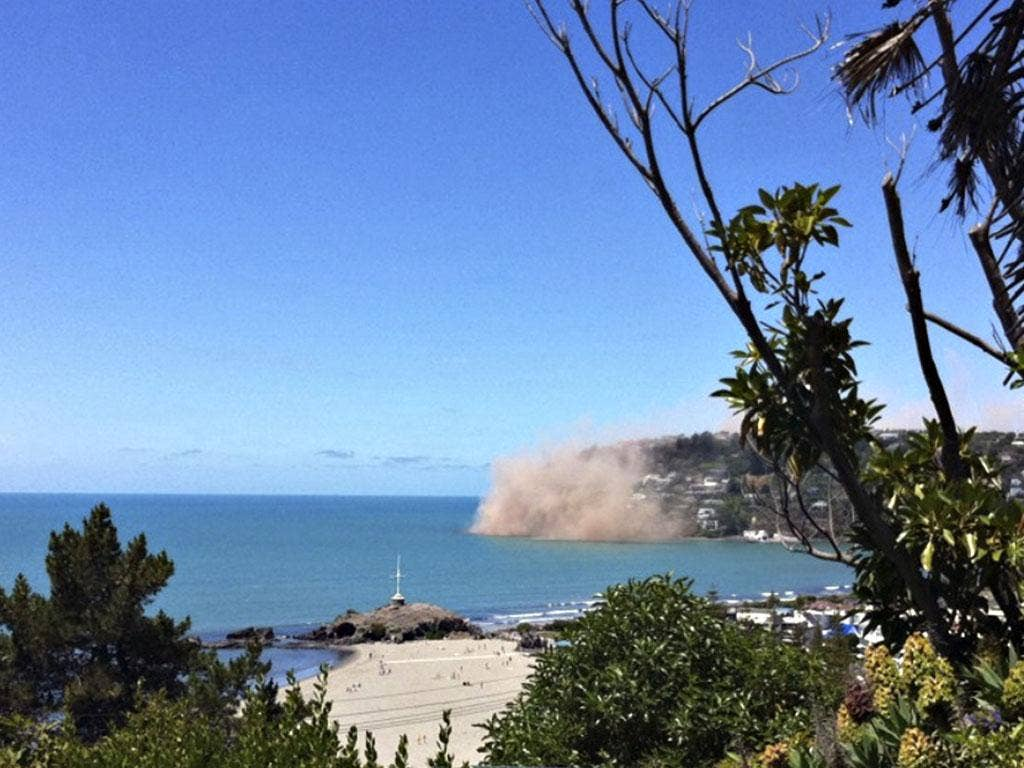 Dust rises from rocks falling from a cliff in the Christchurch suburb of Sumner moments after an earthquake struck