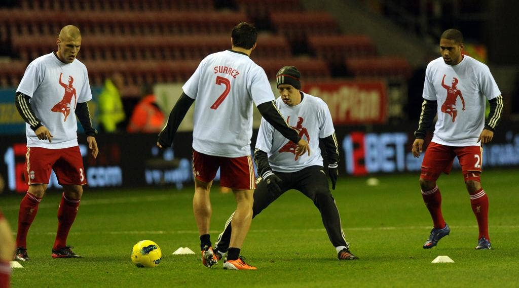 Liverpool players wear T-shirts supporting Luis Suarez, who was banned for racially abusing Manchester United's Patrice Evra