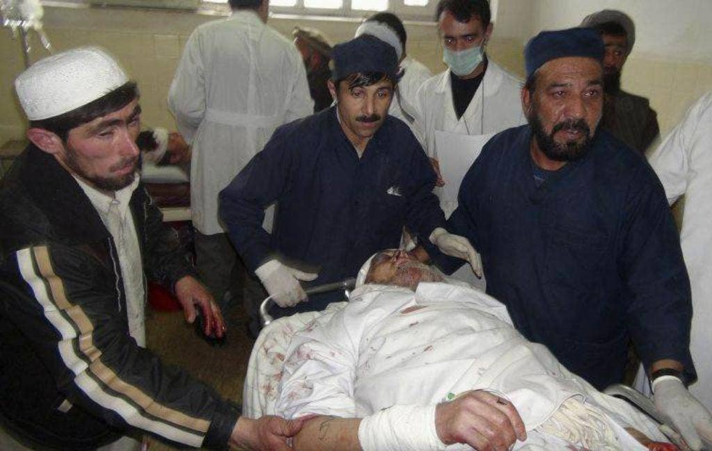 An injured Afghan man receives treatment at a hospital after a suicide attack in Takhar province