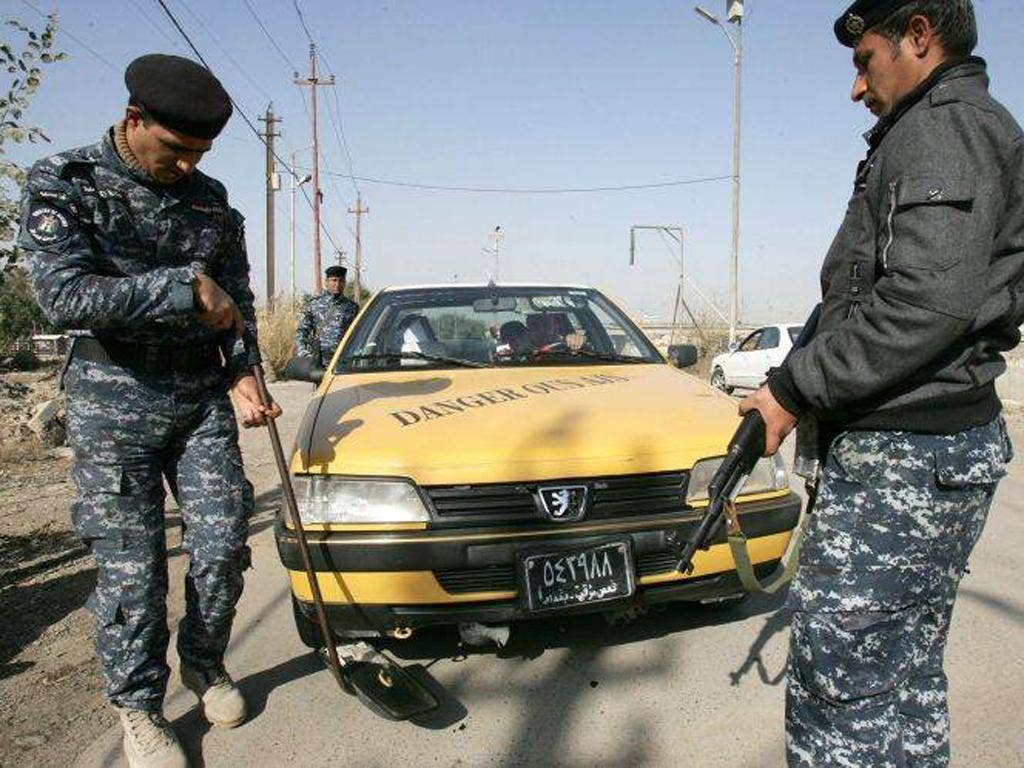 Iraqi policemen check a car at a street in central Baghdad