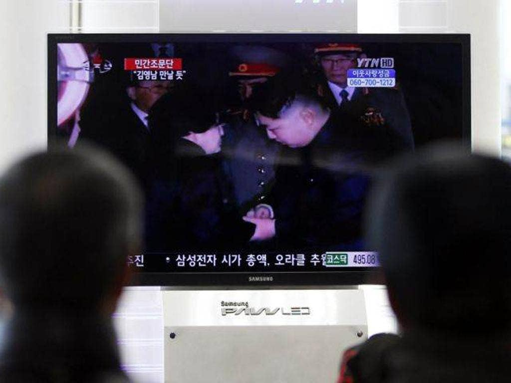 South Koreans watch a TV screen showing Kim Jong-un, right, greet the wife of former South Korean President Kim Dae-jung, Lee Hee-ho