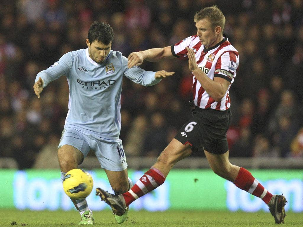 Manchester City's Sergio Aguero (left) vies for the ball against Sunderland's captain, Lee Cattermole, during yesterday's match