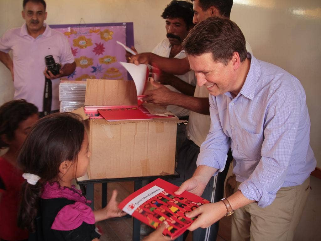 Justin Forsyth, Save the Children's chief executive, hands over school supplies in the West Bank
