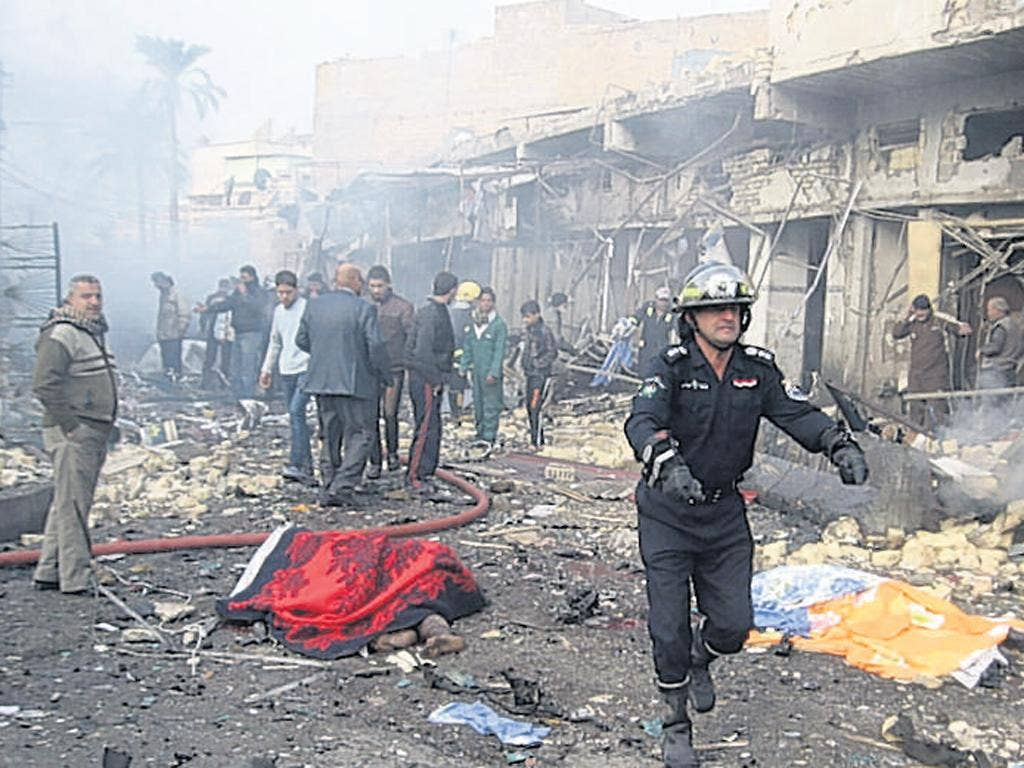 The aftermath of a blast in the Kadhimiya district of Baghdad, where two car bombs exploded killing at least 15 people, according to police and hospitals