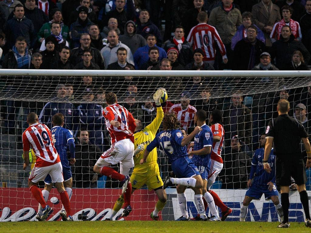 Stoke defender Robert Huth heads his team's third goal during a satisfying win for Tony Pulis against Gillingham at his old stomping ground