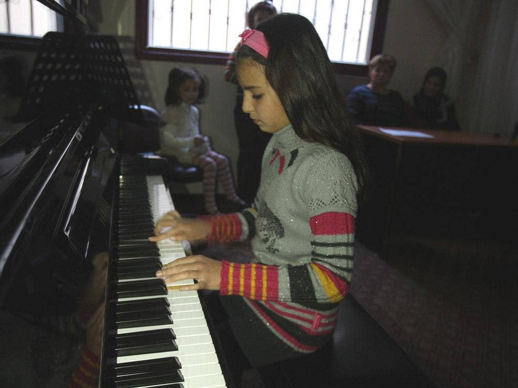 Children hone their skills at the Gaza Music School, watched by staff