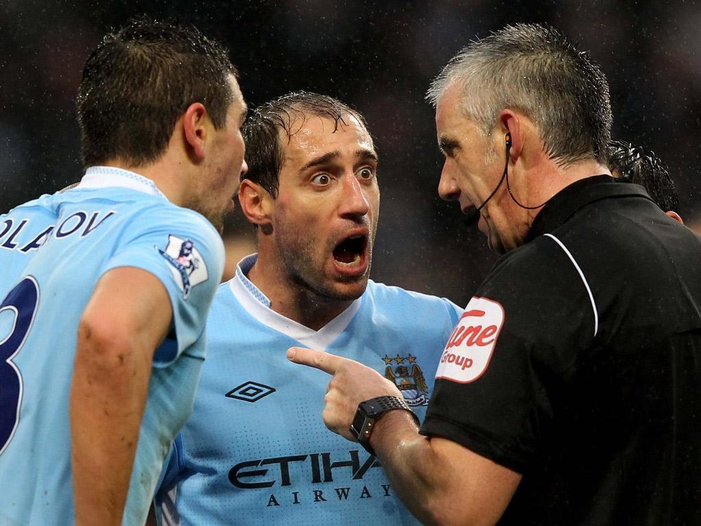 Aleksandar Kolarov and Pablo Zabaleta disagree with referee Chris Foy yesterday