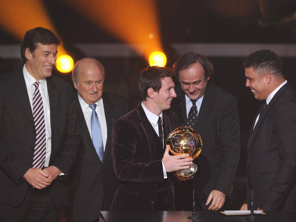 Lionel Messi receives the Ballon d'Or from Uefa president Michel Platini (centre) and former Brazilian player Ronaldo