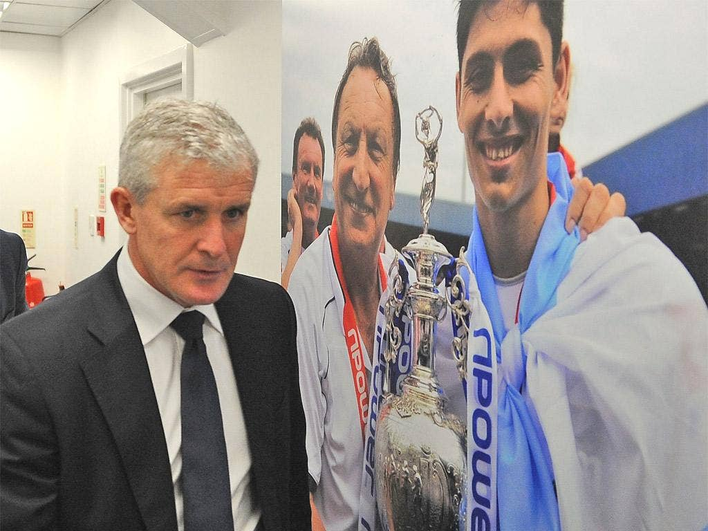 Mark Hughes walks past a picture of his predecessor Neil Warnock at Loftus Road yesterday