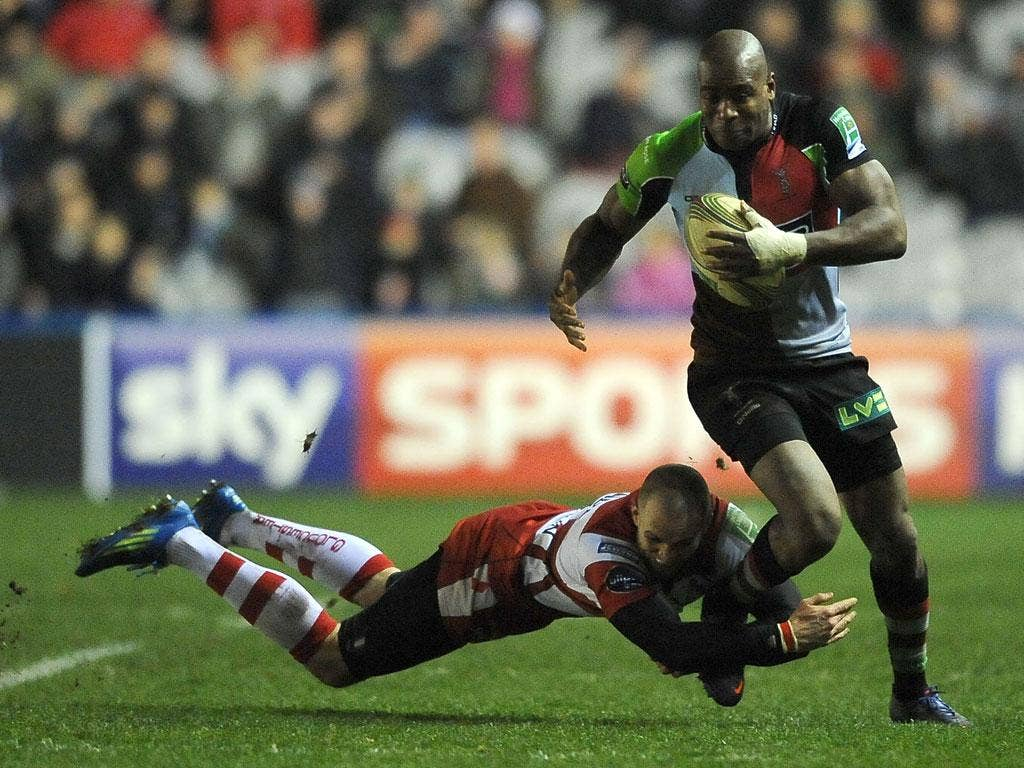 Ugo Monye of Harlequins is tackled by Gloucester's Charlie Sharples at the Stoop
