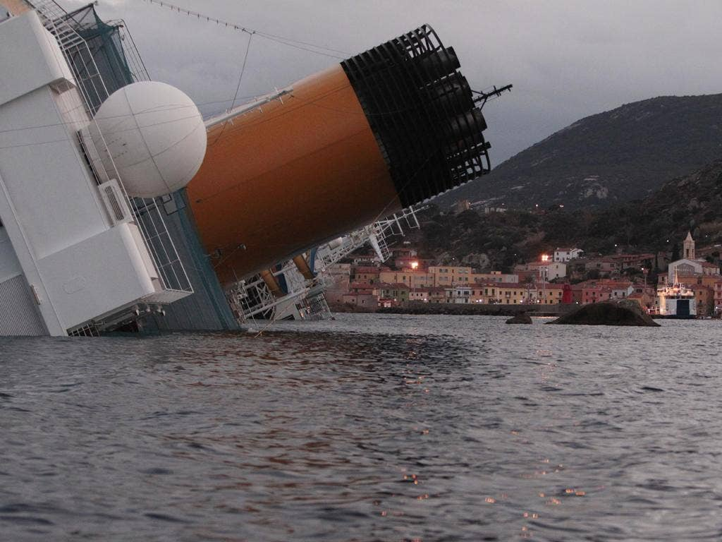 The listing hull of the Costa Concordia looms over Giglio harbour last night