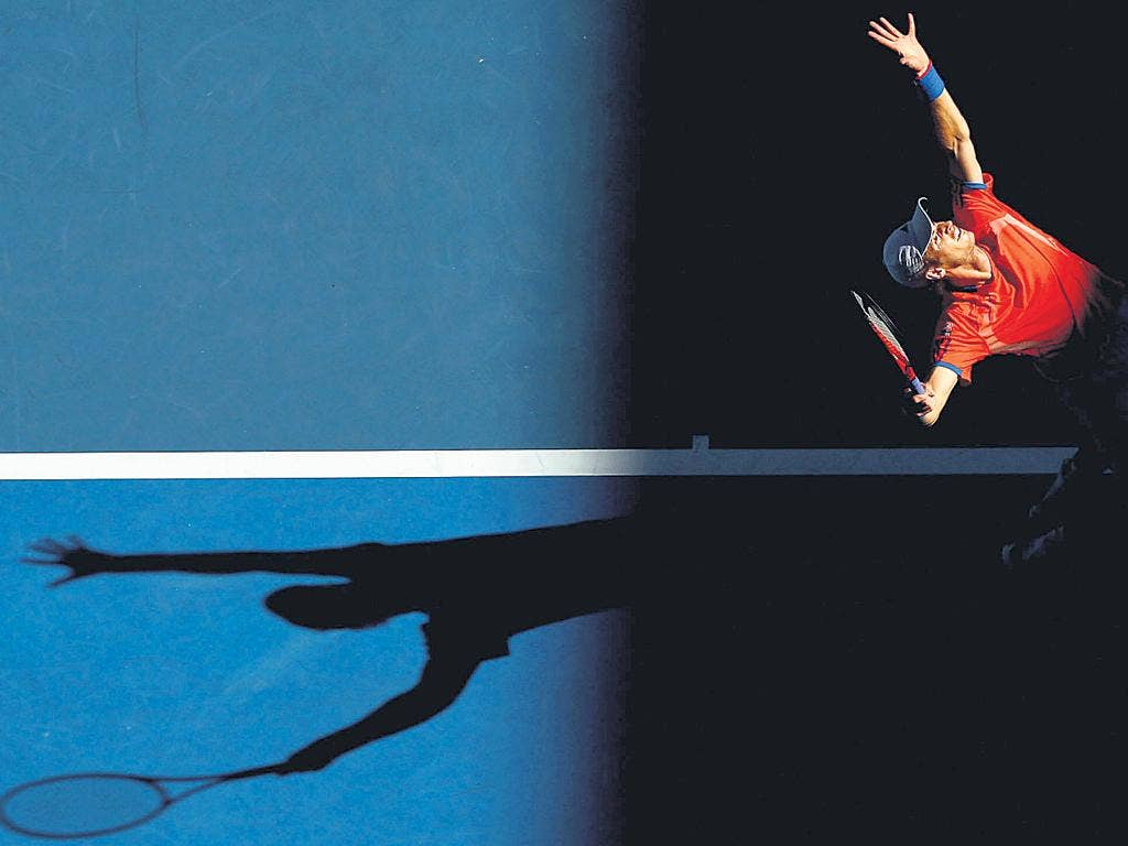 Shadow play: Andy Murray serves on his way to victory over Michaël Llodra in Melbourne