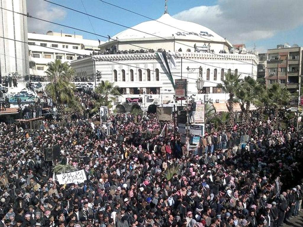 Outside Damascus, thousands mourned the deaths of 11 residents