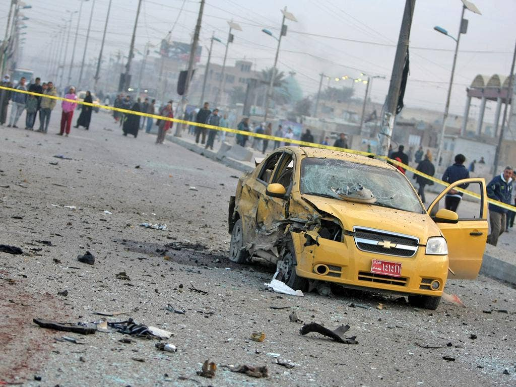 A destroyed car sits in a cordoned-off area as Iraqi security forces inspect the site of a blast after a bomb ripped through a group of workers in Sadr City in Baghdad