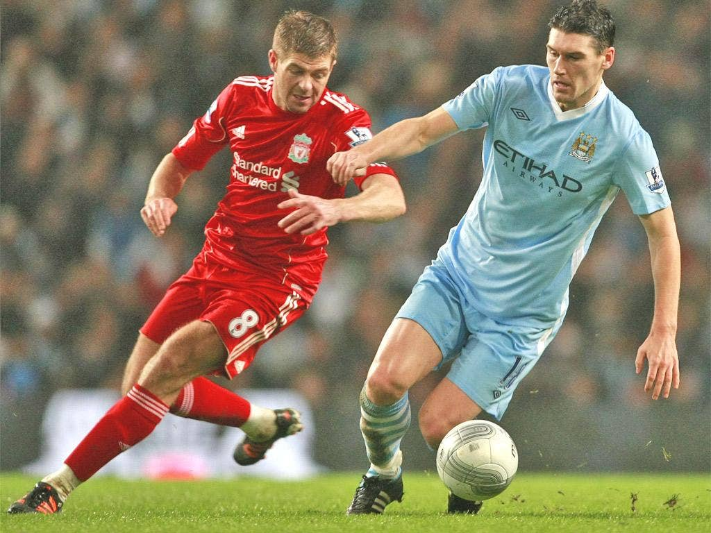 Gerrard and Barry battle for the ball during the first leg encounter