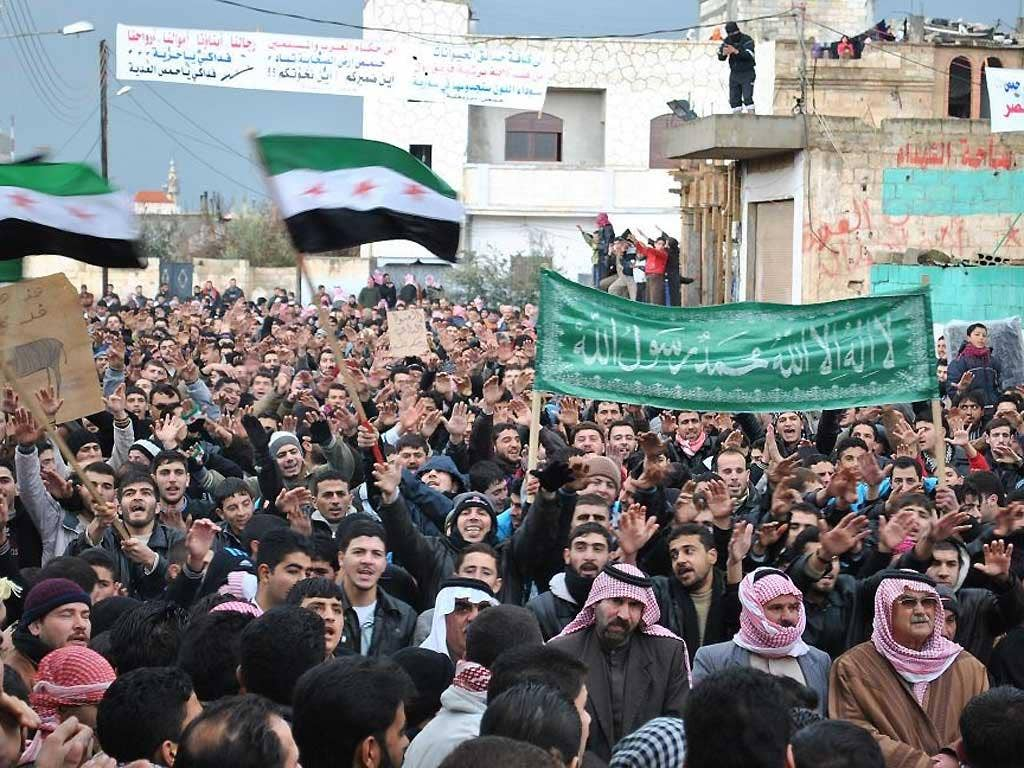 Anti-Syrian regime protesters demonstrate against Syrian President Bashar Assad in the Deir Baghlaba area in Homs province