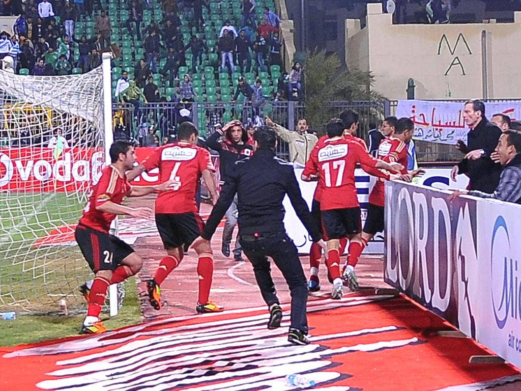 Visiting Al-Ahly players escape from the field after the match in Port Said