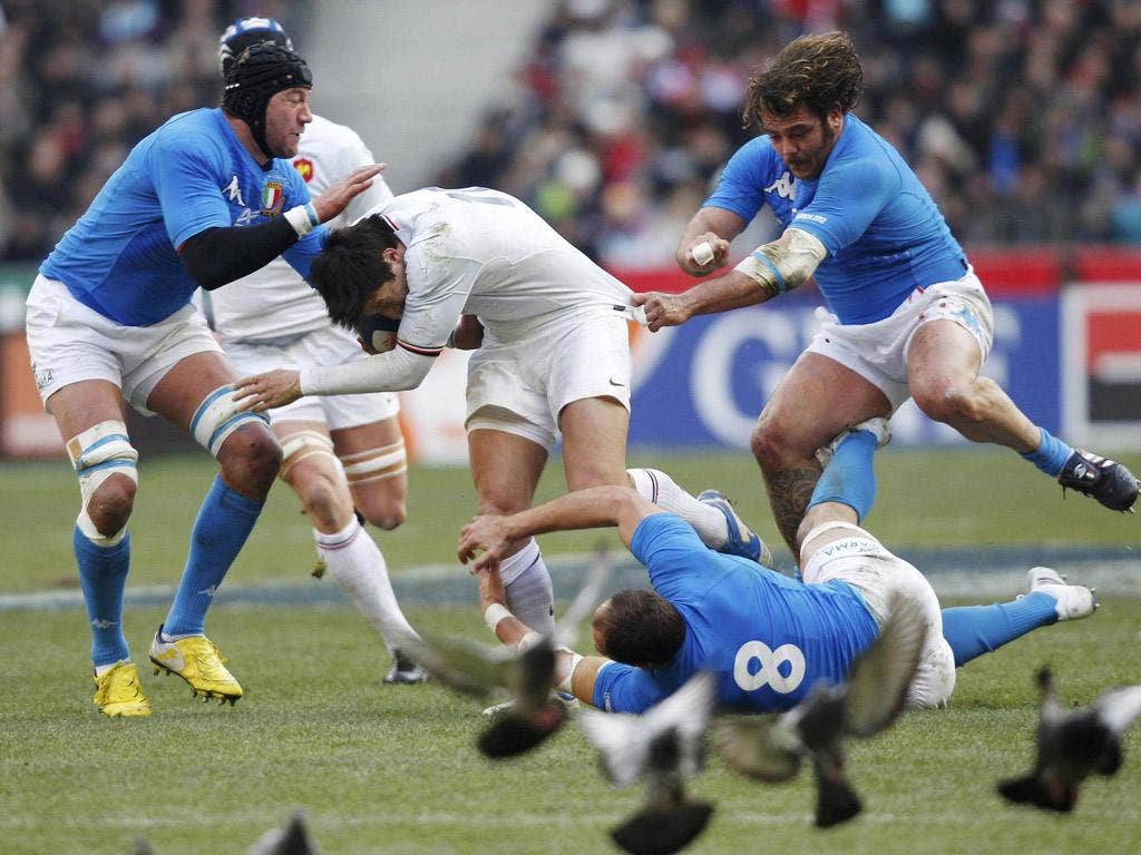 Le crunch: France's François Trinh-Duc is tackled by Sergio Parisse, Cornelius van Zyl and Andrea lo Cicero in Paris
