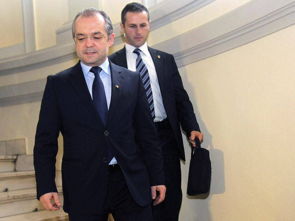Emil Boc leaves the Democratic Liberal Party's office after resigning