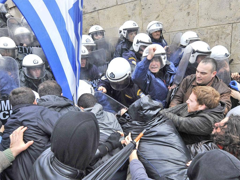 Protesters clash with riot police during the 24-hour general strike in Athens yesterday