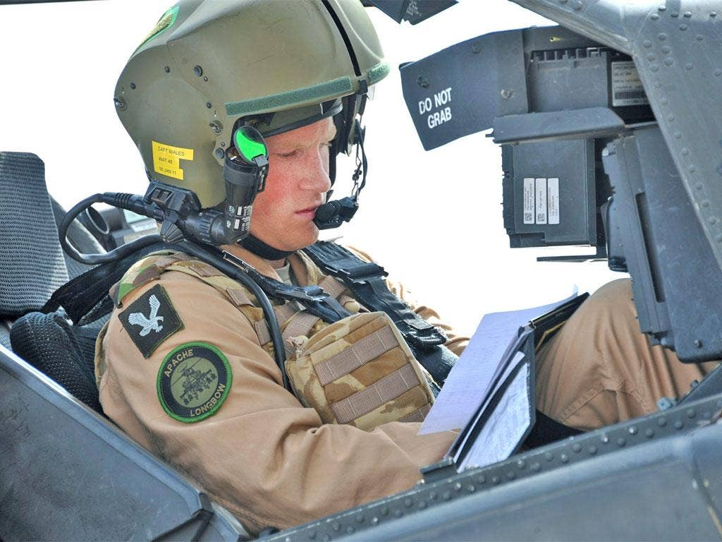 Prince Harry prepares for a training mission in an Apache helicopter