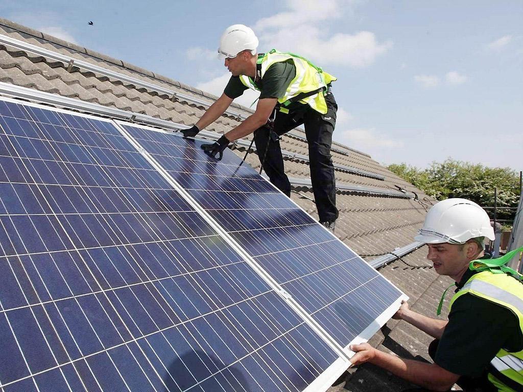 A 2011 photograph of workmen installing solar panels on homes in Delabole near Bodmin