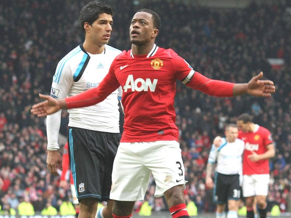 Patrice Evra celebrates in front of Luis Suarez after the final whistle on Saturday