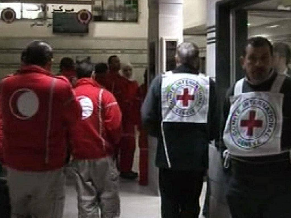 An image grab taken off the official Syrian TV shows Red Crescent and Red Cross medics at a hospital in the Syrian city of Homs as they attempt to evacuate Syrians wounded in shelling by regime forces
