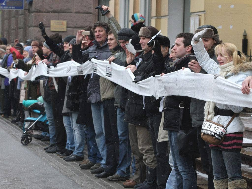 Opposition supporters carry white ribbons during the rally in Moscow