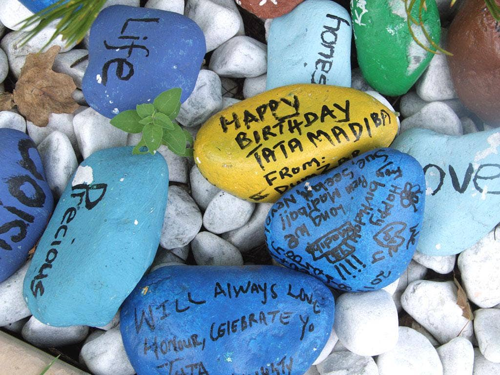 Painted pebbles with messages placed outside Mr Mandela's home