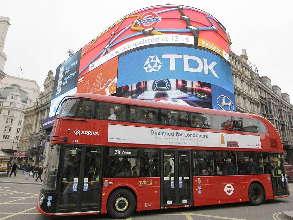 A new routemaster double decker bus passes Piccadilly Circus in London on its first first day of service