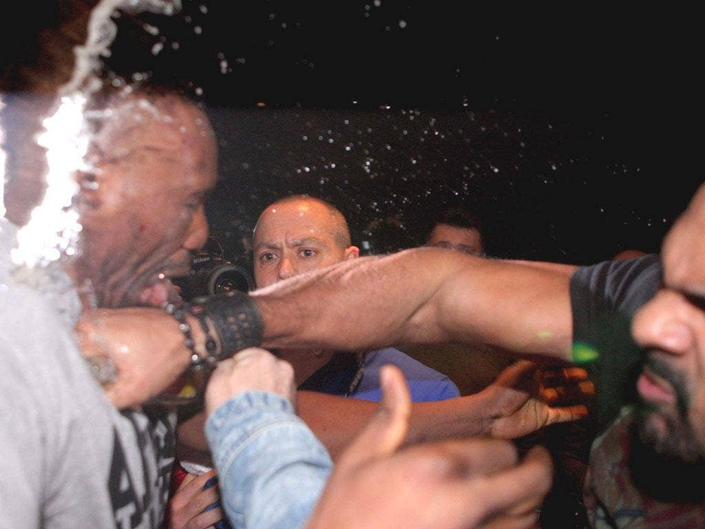 David Haye (right) hits Dereck Chisora during their press conference brawl in Germany