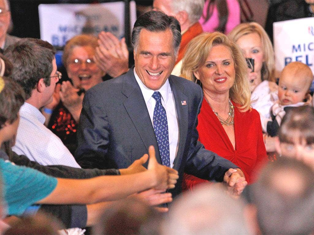 Mitt Romney, with his wife Ann, shakes hands with supporters in Novi, Michigan