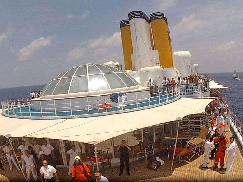Passengers and crew take shelter on the deck of the Costa Allegra