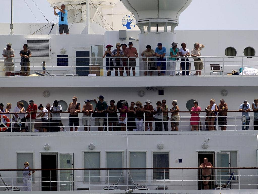 Passengers look out of the Costa Allegra cruise ship as it arrives in the Seychelles