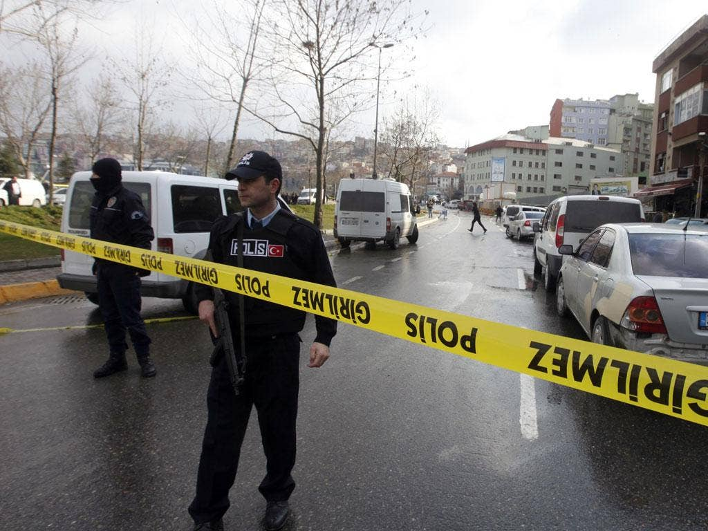 Police officers stand guard at the scene where the bomb explosion took place in Istanbul