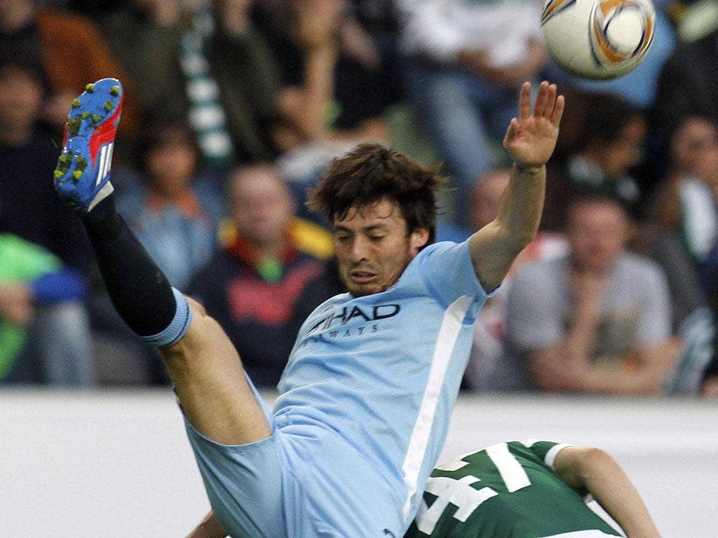 Manchester City's David Silva tussles with Sporting Lisbon's Joao Pereira last night