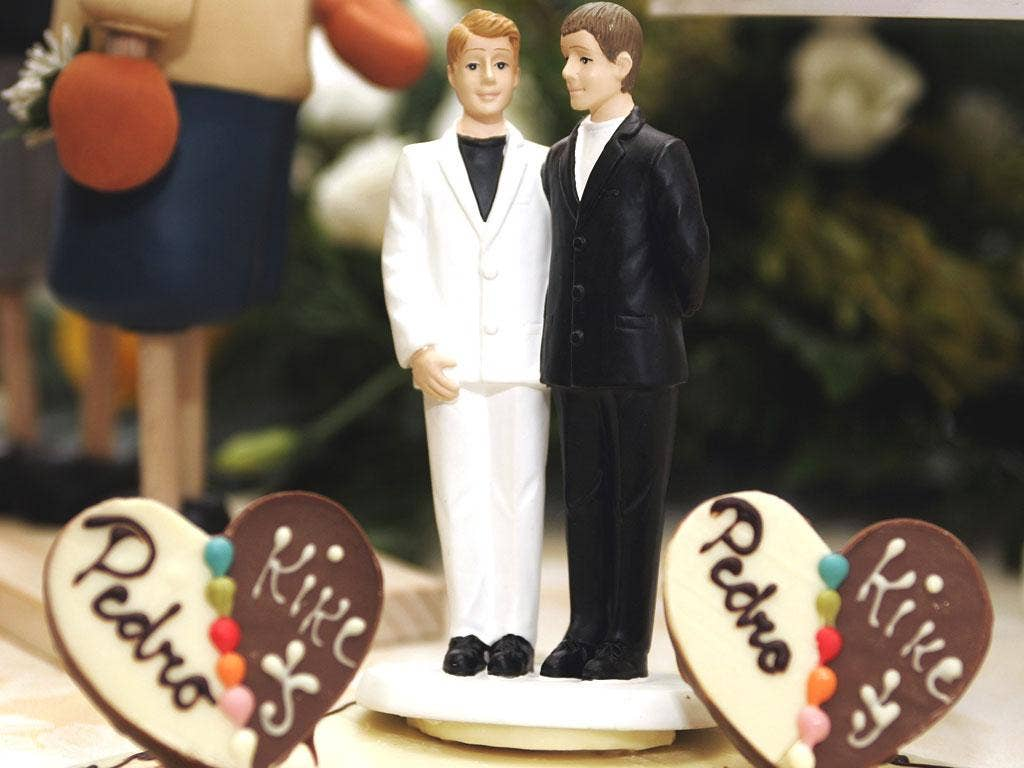 A wedding cake figurine of a same-sex couple made up of two men
